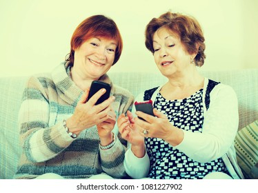 Smiling senior women sitting with smartphones in living room