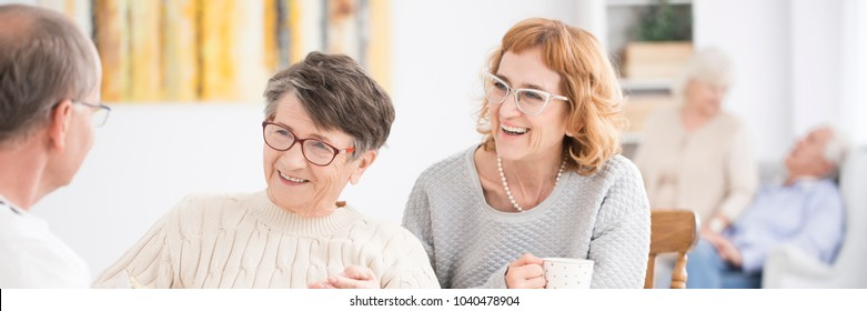 Smiling senior women talking to a friend during a meeting in a nursing home
