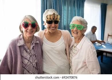 Smiling senior women wearing novelty glasses standing at nursing home