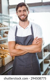 Smiling server in apron arm crossed at the bakery