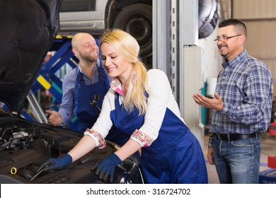 Smiling service crew and satisfied driver standing near car indoor. Focus on woman