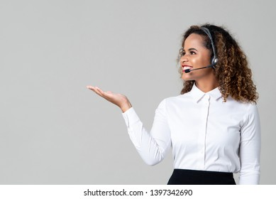 Smiling service minded African American woman wearing headphones as a call center staff with hand open on light gray background