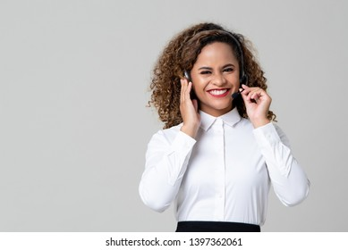Smiling service minded African American woman wearing headphones as a call center staff studio shot on light gray background