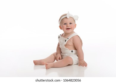 A smiling seven month old baby girl wearing white overalls. Shot in the studio on a white, seamless backdrop.
