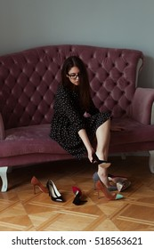 Smiling sexy beautiful brunette girl in glasses choosing a pair of high heels shoes.  Sitting on pink velvet elegant sofa. Hard choice.  Beautiful legs. Shopping at store. Choosing perfect pair