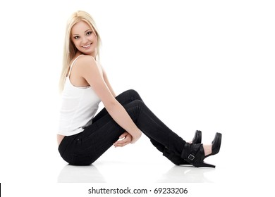 Smiling sexy blond woman in white shirt and  jeans sitting on a floor isolated on white