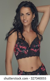 Smiling sexy female in dark bra isolated on grey background.