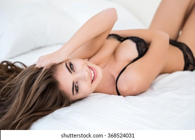 Smiling sexy woman in lingerie relaxing on the bed