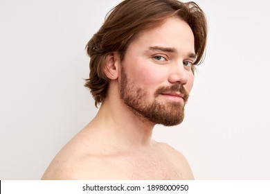 smiling shirtless man having bristle looking at camera, young caucasian male model isolated over white background. side view portrait