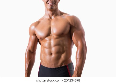 Smiling shirtless muscular man standing over white background