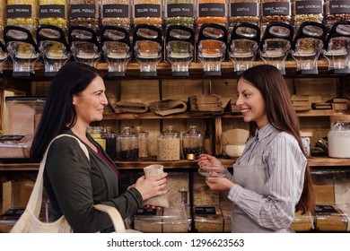 Smiling shop assistant and customer standing against each other in package free grocery store. Zero waste shopping -  shopkeeper serving customer in plastic free shop.