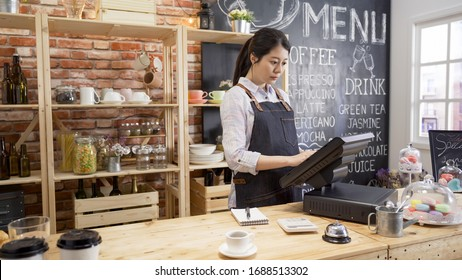 smiling shop assistant using pos point of sale terminal to put in order from note at restaurant register. young girl waitress standing in wooden bar counter and working on digital tablet in cafe