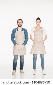 smiling shop assistants in aprons looking at camera isolated on white