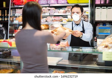 Smiling shopkeeper serving a customer while wearing a mask, coronavirus pandemic concept