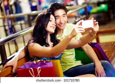 Smiling shoppers taking a picture of themselves