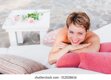 Smiling short-haired woman laying on white sofa in outdoor cafe