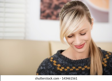 Smiling and shy beautiful blond woman looking down in a coffee shop wearing a knitwear sweater