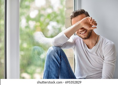 Smiling shy man close face with hand sitting on window sill
