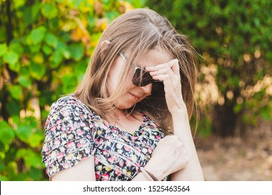 Smiling shy young woman looking down while holding one hand to her forehead outdoors - Cute girl with brown hair wearing sunglasses feeling embarrassed and trying to cover her face in the park