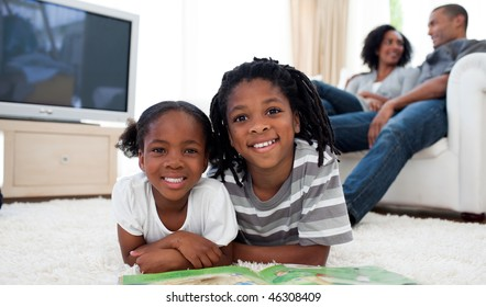 Smiling siblings reading lying on the floor in the living room