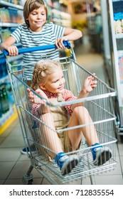 smiling siblings with shopping cart having fun in supermarket