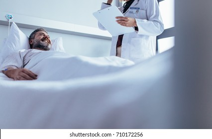 Smiling sick man lying in bed with doctor standing by. Nurse visiting male patient in hospital ward.