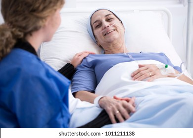 Smiling sick woman enjoying a visit of her caregiver supporting her during chemotherapy