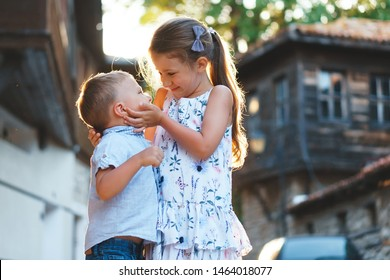 smiling sister holding brother's face in hands in sunlight
