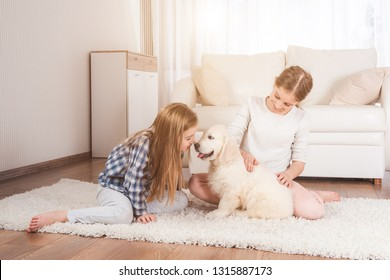 Smiling sisters sit together on carpet with cute retriever puppy