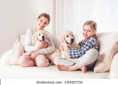 Smiling sisters sitting with cute fluffy puppies on sofa