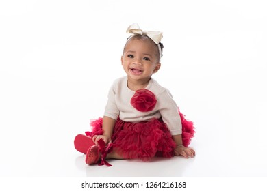 A smiling six month old baby girl wearing a red tutu. She is sitting on a white, seamless background.
