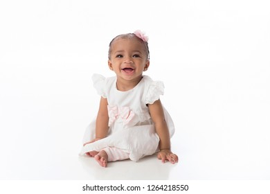 A smiling six month old baby girl wearing a white dress. She is sitting on a white, seamless background.