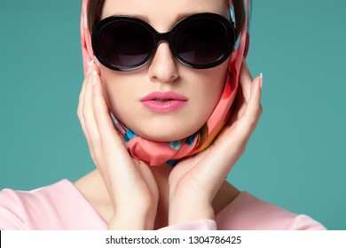 Smiling sixties style woman with scarf and sunglasses.