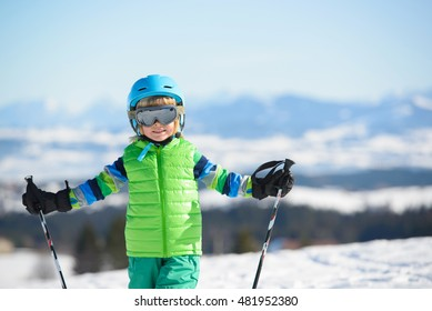 Smiling skier boy has fun in the mountains on a sunny day