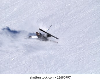 A smiling skier fall on the ski slope.