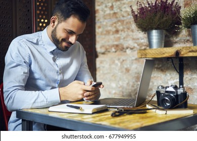Smiling skilled blogger watching video in social networks typing feedback using modern smartphone, positive designer texting message on mobile getting new offer on email box for making project