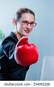 smiling skinny winning business woman with a red box glove
