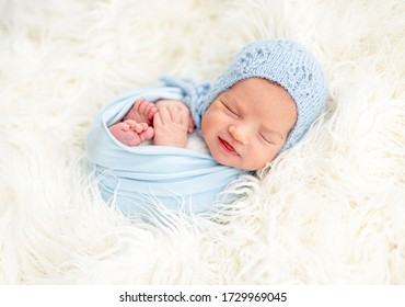 Smiling sleeping newborn in knitted blue hat