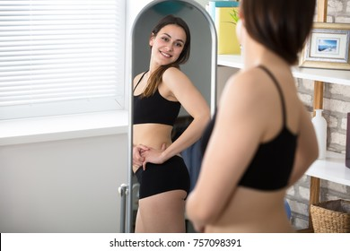 Smiling Slim Woman Looking At Her Reflection In Mirror