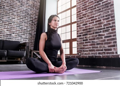 Smiling slim young woman doing stretching exercise for inner thighs sitting in butterfly yoga pose in stylish loft studio