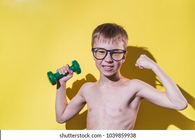 Smiling small boy in glasses holding dumbbell in hand.  Funny sport concept.