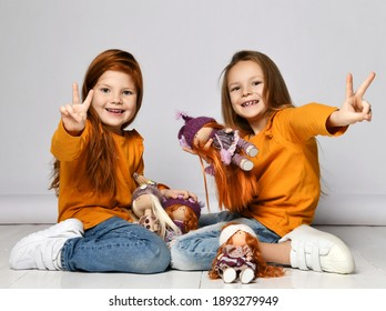 Smiling small girls sisters in yellow comfortable longsleeves, jeans and sneakers sitting on floor playing with toy dolls and showing peace signs over white background. Happy childhood, stylish look