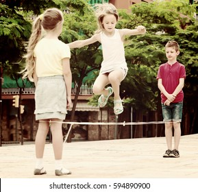 Smiling small kids in school age playing together with chinese jumping rope outdoors. Focus on boy