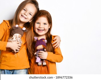 Smiling small pretty girls sisters or friends in terracotta yellow comfortable longsleeves standing hugging holding toy dolls in hands over white background, copy space. Happy childhood, stylish look