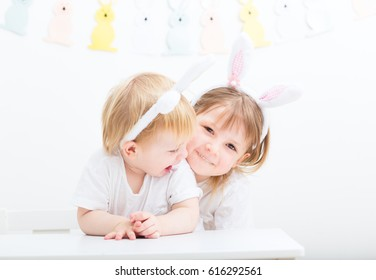 smiling small toddler boy and his older sister sitting together at light interior home, easter preparation with kids. siblings happily playing indoors. preschooler children wearing rabbit ears.