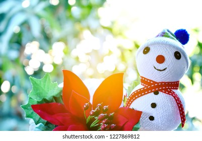 Smiling snow man put on a wool hat with red Christmas flower on bokeh background and sunlight.