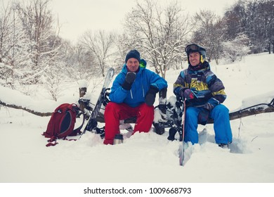 Smiling snowboarders are drinking coffee from thermos in the forest after freeride, among snow covered trees and having fun. Epic adventure in wilderness.