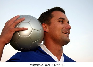 Smiling soccer player holding the ball with one hand
