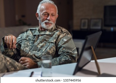 Smiling soldier in military uniform looking at framed photo on his desk and feeling nostalgic.
