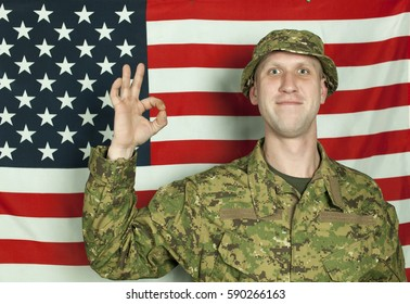 Smiling soldier stand against  American flag  with international sjgn everything well